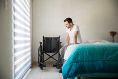 Deprimierter Mann nahe bei einem Rollstuhl Lizenzfreies Stockfoto