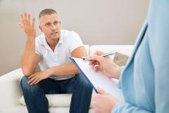 Deprimierter Patient vor Psychiater Lizenzfreie Stockfotografie