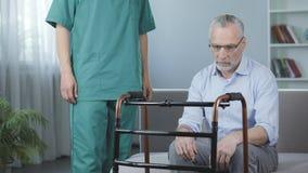 Deprimierter Pensionär, der auf Couch sitzt und gehenden Rahmen, Pflegeheim betrachtet Stockbilder