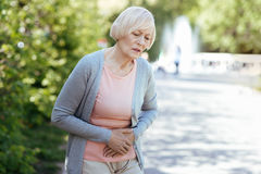 Deprimierter Pensionär, der Magenschmerzen draußen hat lizenzfreies stockbild