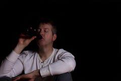 Deprimierter reifer Mann, der ein Bier im dunklen Hintergrund trinkt Lizenzfreie Stockbilder