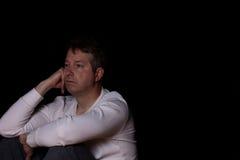 Deprimierter reifer Mann, der im dunklen Hintergrund denkt Lizenzfreie Stockfotos
