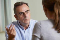 Deprimierter reifer Mann, der mit Ratsmitglied spricht Lizenzfreies Stockfoto