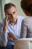 Deprimierter reifer Mann, der mit Ratsmitglied spricht Stockfotos