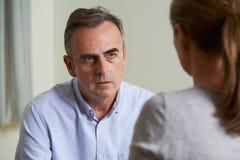 Deprimierter reifer Mann, der mit Ratsmitglied spricht Stockbild