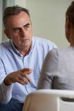 Deprimierter reifer Mann, der mit Ratsmitglied spricht Stockfoto