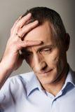 Deprimierter reifer Mann, der seinen Kopf berührt Lizenzfreies Stockfoto