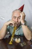 Deprimierter reifer Mann in einer Parteieinstellung Stockfotografie
