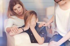Deprimierter Schüler, der das Erhalten der Unterstützung von seiner Mutter und von Psychologen hat Stockfoto