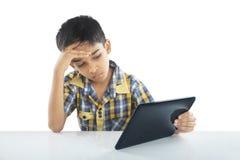 Deprimierter Schuljunge mit Tablette Stockfoto