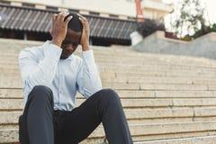 Deprimierter schwarzer Geschäftsmann mit den Händen auf dem Kopf, der auf Treppe sitzt Lizenzfreies Stockbild