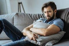 Deprimierter schwermütiger Mann, der auf dem Sofa stillsteht Stockfotografie