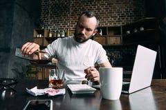 deprimierter strömender Whisky des jungen Mannes im Glas nach Auseinanderbrechen mit Freundin stockfotos