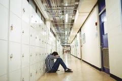 Deprimierter Student, der im Umkleideraum sitzt Stockbild