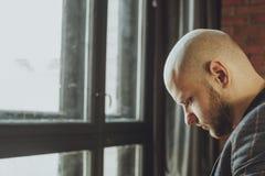 Deprimierter trauriger Mann senkte seinen Kopf und Stellung nahe Fenster Stockbild