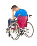 Deprimierter und behinderter Mann, der auf einem Rollstuhl sitzt Stockfotografie