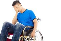 Deprimierter und behinderter Mann, der auf einem Rollstuhl sitzt Lizenzfreie Stockfotografie