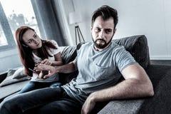 Deprimierter unshaken Mann, der von seiner Frau sitzt und sich abwendet Lizenzfreies Stockfoto