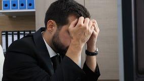 Deprimierter Unternehmer in seinem Büro atmet aus und setzt seins ein, das in Hände hed ist