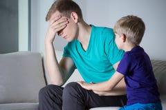 Deprimierter Vater, der auf Couch sitzt Lizenzfreie Stockbilder