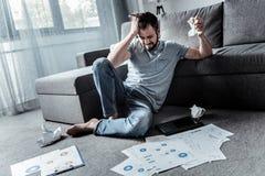 Deprimierter verärgerter Mann, der nicht mit seiner Arbeit fertig wird Lizenzfreies Stockfoto