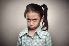 Deprimiertes asiatisches Kind, das ihr unglückliches Gesicht zeigt Stockbild