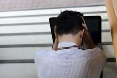 Deprimiertes betontes junges asiatisches Geschäftsmann-Bedeckungsgesicht mit seinen Händen und Gefühl ermüdet und erschöpft Lizenzfreie Stockbilder