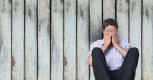 Deprimiertes Geschäftsmannbedeckungsgesicht beim Sitzen gegen hölzerne Wand Stockbild