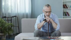 Deprimiertes großväterliches Sitzen auf Couch und Denken an Zukunft, Pflegeheim Lizenzfreies Stockfoto
