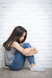 Deprimiertes junges asiatisches Mädchen, das zu Hause auf Boden sitzt Stockbild