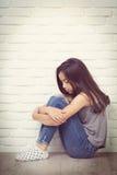 Deprimiertes junges asiatisches Mädchen, das zu Hause auf Boden sitzt Stockbilder