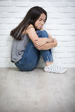 Deprimiertes junges asiatisches Mädchen, das zu Hause auf Boden sitzt Lizenzfreie Stockfotografie