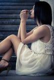 Deprimiertes junges Sitzen der erwachsenen Frau Stockbilder