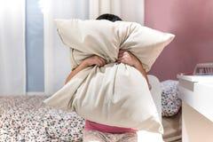 Deprimiertes Kind, das ihr Gesicht mit Kissen bedeckt und in ANG schreit Lizenzfreie Stockfotos