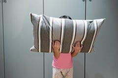 Deprimiertes Kind, das ihr Gesicht mit Kissen bedeckt und in ANG schreit Stockfotos