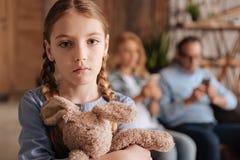 Deprimiertes kleines Mädchen, das zu Hause Traurigkeit ausdrückt Stockfotos