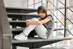 Deprimiertes kleines Mädchen, das zuhause auf Treppe sitzt Lizenzfreie Stockfotografie