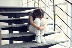 Deprimiertes kleines Mädchen, das zuhause auf Treppe sitzt Stockfotos