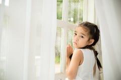 Deprimiertes kleines Mädchen nahe Fenster zu Hause Lizenzfreies Stockfoto