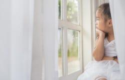 Deprimiertes kleines Mädchen nahe Fenster zu Hause Lizenzfreie Stockbilder
