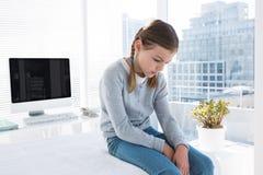 Deprimiertes Mädchen, das auf der Prüfungstabelle sitzt Stockbilder