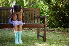 Deprimiertes Mädchen, das auf Holzbank mit Kopf in den Händen sitzt Stockfotos