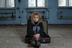 Deprimiertes Mädchen, das im Koffer sitzt Lizenzfreie Stockfotos