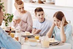 Deprimiertes Mädchen, das mit ihrer Familie frühstückt Stockbilder