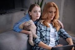 Deprimiertes Mädchen, das zu Hause beschäftigte Mutter umarmt Stockbild