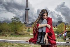 Deprimiertes Mädchen in einem roten Poncho, der auf einer Bank allein sitzt Lizenzfreies Stockbild