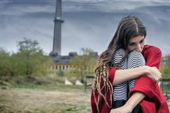 Deprimiertes Mädchen in einem roten Poncho, der auf einer Bank allein sitzt Stockbilder
