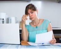 Deprimiertes Mädchen mit Dokumenten an der Küche Stockfoto