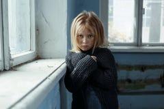 Deprimiertes poot Mädchen, das nahes Fenster steht Stockfotografie