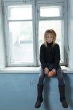 Deprimiertes poot Mädchen, das nahes Fenster steht Lizenzfreie Stockfotos